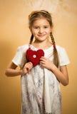 Niña linda que lleva a cabo el corazón rojo decorativo Fotografía de archivo