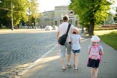 Niña linda que lleva a cabo la mano de su padre durante paseo de la ciudad del verano imagen de archivo libre de regalías