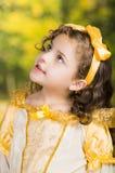 Niña linda que lleva el vestido amarillo hermoso con la banda principal a juego, presentando para la cámara, fondo verde del bosq Imagen de archivo libre de regalías