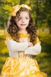 Niña linda que lleva el vestido amarillo hermoso con la banda principal a juego, presentando para la cámara, fondo verde del bosq Fotografía de archivo libre de regalías