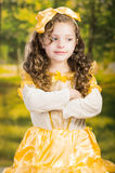 Niña linda que lleva el vestido amarillo hermoso con la banda principal a juego, presentando para la cámara, fondo verde del bosq Foto de archivo