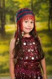 Niña linda que lleva el vestido rojo hermoso con el sombrero a juego de la perla, presentando para la cámara, fondo verde del bos Foto de archivo