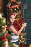 Niña linda que lleva la venda roja que sostiene el regalo cerca del árbol de navidad foto de archivo