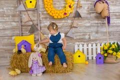 Niña linda que lleva los vaqueros rústicos que juegan escondite con un pollo que se sienta en un pajar El concepto de niños con fotografía de archivo libre de regalías