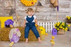 Niña linda que lleva los vaqueros rústicos que juegan escondite con un pollo que se sienta en un pajar El concepto de niños con foto de archivo