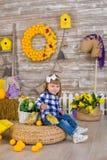 Niña linda que lleva los vaqueros rústicos que juegan escondite con un pollo que se sienta en un pajar El concepto de niños con fotografía de archivo