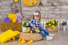 Niña linda que lleva los vaqueros rústicos que juegan escondite con un pollo que se sienta en un pajar El concepto de niños con fotos de archivo libres de regalías