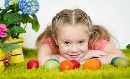 Niña linda que miente con los huevos y las flores de Pascua en el coche verde Fotos de archivo libres de regalías