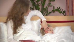 Niña linda que miente en cama mientras que la mujer de la madre leyó el libro del cuento almacen de video