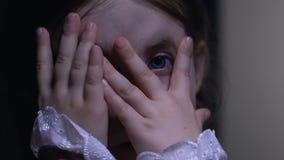 Niña linda que mira a escondidas a través de los fingeres, asustados de contenido adulto prohibido metrajes
