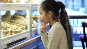 Niña linda que mira la exhibición la panadería local