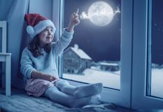 Niña linda que mira la luna el cielo del invierno imagenes de archivo