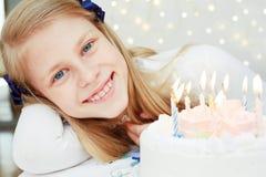 Niña linda que mira la torta con las velas Imagen de archivo