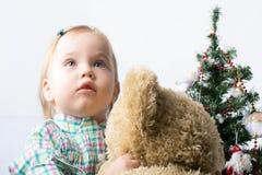Niña linda que mira para arriba y que sostiene un oso de peluche cerca de la C Imagen de archivo