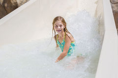 Niña linda que monta abajo de un tobogán acuático en un parque del agua Fotos de archivo libres de regalías