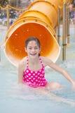 Niña linda que monta abajo de un tobogán acuático en un parque del agua Fotografía de archivo