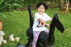 Niña linda que monta un caballo de madera Fotos de archivo libres de regalías