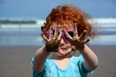 Niña linda que muestra las manos arenosas en la playa de Bali imágenes de archivo libres de regalías