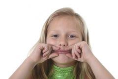 Niña linda que muestra sus labios en las partes del cuerpo que aprenden el serie de la carta de la escuela Imagenes de archivo