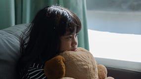 Niña linda que piensa y que sostiene una muñeca, una preocupación y un triste encendido Imagenes de archivo