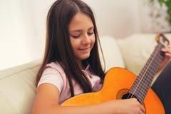 Niña linda que practica sus lecciones de la guitarra imagen de archivo libre de regalías