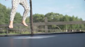 Niña linda que salta en un trampolín en el exterior del verano almacen de metraje de vídeo