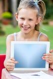 Niña linda que señala en la tableta en blanco al aire libre Imagen de archivo