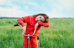 Niña linda que se coloca con una bicicleta en verano Foto de archivo