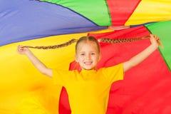 Niña linda que se coloca debajo del paracaídas colorido Fotografía de archivo