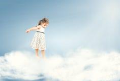Niña linda que se coloca descalzo en las nubes Imagen de archivo