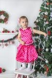 Niña linda que se coloca en una silla cerca del árbol de navidad Imagenes de archivo