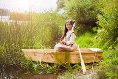 Niña linda que se divierte en un barco por un río Fotos de archivo libres de regalías