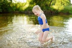 Niña linda que se divierte en una playa arenosa del lago en día de verano caliente y soleado Niño que juega por el río foto de archivo