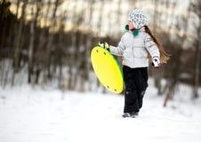 Niña linda que se ejecuta en la nieve con el platillo Fotos de archivo libres de regalías