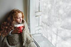 Niña linda que se sienta con una taza de cacao caliente por la ventana a imagen de archivo