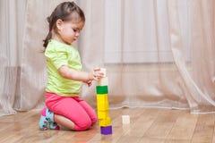 Niña linda que se sienta en el piso y que juega con el edificio Fotografía de archivo libre de regalías