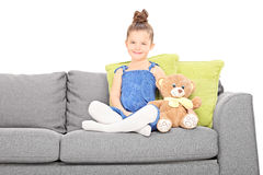 Niña linda que se sienta en el sofá con el oso de peluche Imagen de archivo