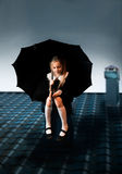 Niña linda que se sienta en el tejado con un paraguas Fotografía de archivo libre de regalías