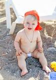 Niña linda que se sienta en la arena y los juegos fotos de archivo