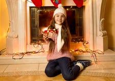 Niña linda que se sienta en la chimenea con el regalo de la Navidad Fotos de archivo libres de regalías