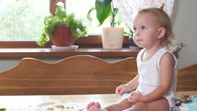 Niña linda que se sienta en la tabla de cocina almacen de metraje de vídeo