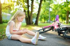 Niña linda que se sienta en la tierra después de caer apagado su bici en el parque del verano Niño que consigue daño mientras que imagen de archivo