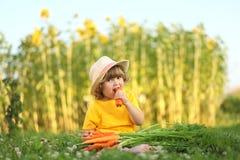 Niña linda que se sienta en una hierba verde que come la zanahoria Imagen de archivo libre de regalías