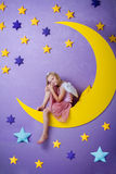 Niña linda que se sienta en una luna grande Imagenes de archivo
