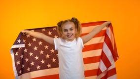 Niña linda que sostiene la bandera americana, animando para el equipo de deportes preferido, juego fotografía de archivo libre de regalías