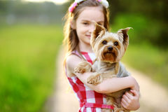 Niña linda que sostiene su perro del terrier de Yorkshire foto de archivo libre de regalías