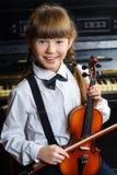 Niña linda que sostiene un violín interior Imagen de archivo