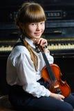 Niña linda que sostiene un violín interior Fotos de archivo libres de regalías