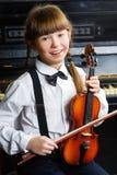 Niña linda que sostiene un violín interior Imagen de archivo libre de regalías