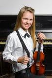 Niña linda que sostiene un violín interior Foto de archivo libre de regalías